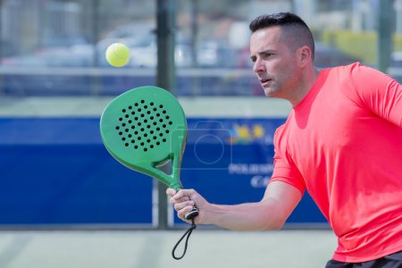 man playing paddle tennis outdoors