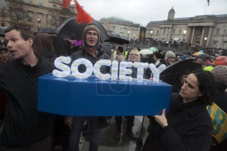"""Thatcher Death Party, London, UK.13.04.2013 Protesters congregate on Trafalgar Square, to celebrate death of Margaret Thatcher. Man hold coffin with letter """"society"""""""