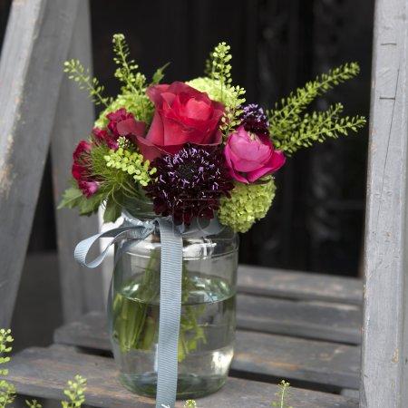 Bouquet of hydrangea, carnations and hydrangeas in a glass jar o