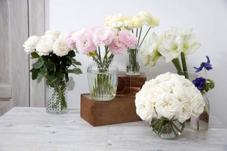 Photo for White roses, ranunculus, blue anemones, yellowish buttercups, lilies in round vases on the wooden boxes on the table for a special occasion as a kitchen decoration. - Royalty Free Image