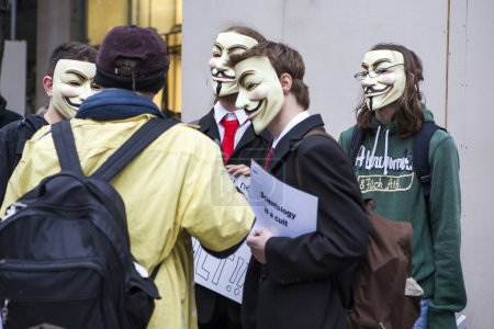 """A protester wearing a Guy Fawkes mask holds a placard """"Tax Scientology"""""""