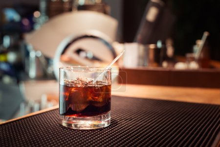 Photo for Black russian cocktail on the bar stand on rubber mat. Shallow DOF and marsala tonned - Royalty Free Image