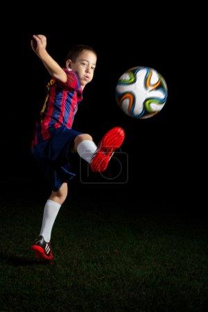 Low key portrait of a boy kicking a world cup football
