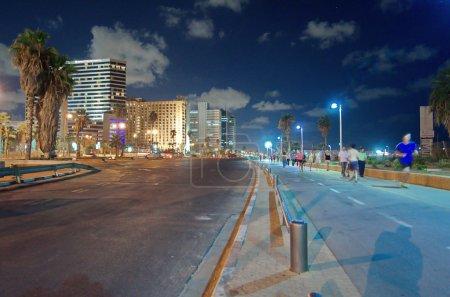 Foto de Tel aviv, sept 7, 2014: gran angular larga vista de exposición de la tel aviv, israel paseo marítimo en la noche con gente borrosa y jinetes y Torres en el fondo. - Imagen libre de derechos