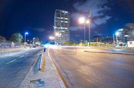 Foto de Gran angular larga vista de exposición de la tel aviv, israel paseo marítimo en la noche con gente borrosa y jinetes y Torres en el fondo. - Imagen libre de derechos
