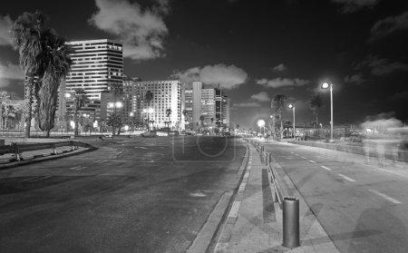 Foto de Visión de larga exposición blanco y negro de gran angular de la tel aviv, israel paseo marítimo por la noche con gente borrosa y jinetes - Imagen libre de derechos