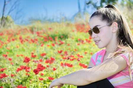 Photo pour Teenage girl with braces on her teeth in a field of wild red anemone coronaria (windflower)  flowers blooming in the Galilee, Israel, after the winter rains - image libre de droit