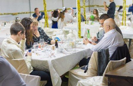 Photo pour Maalot, Israël - 27 septembre 2015: Personnes ayant un dîner festif de Souccot dans un grand Soucca (souccah) en Galilée dans le nord d'Israël - image libre de droit