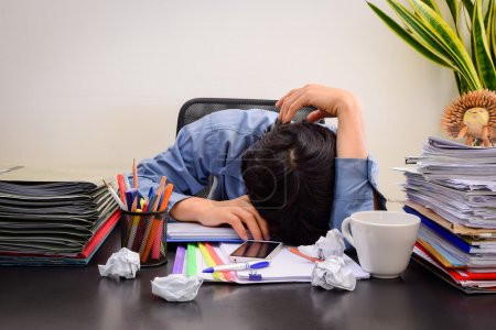Businessman asleep at office desk with finance sheet calculator and coffee.