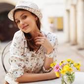 Dívka sedí u stolu v klobouku