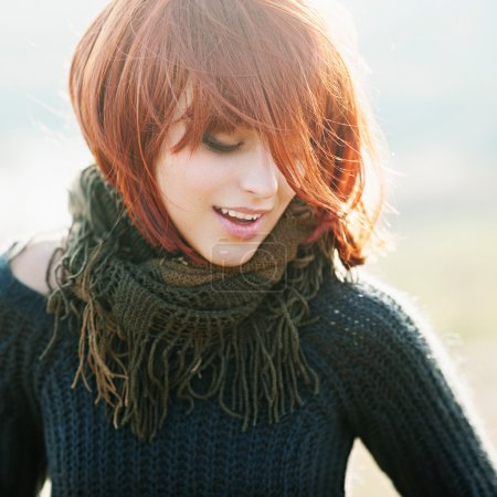 Portrait of beautiful young girl with red hair in a field wearing a warm pullover, lifestyle