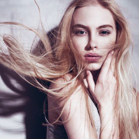 Photo for Portrait of beautiful young blonde woman with blowing hair on gray studio background - Royalty Free Image