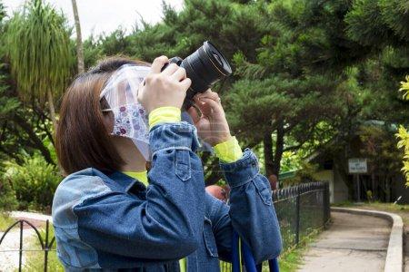 Photo pour Une femme asiatique portant un masque facial et un bouclier tente de prendre une photo avec un appareil photo reflex. - image libre de droit
