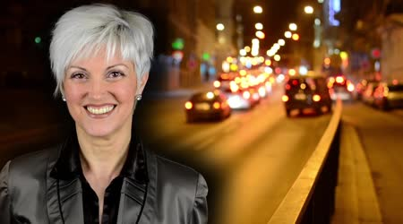 Business middle aged woman smiles - night city - night street with cars - lamps - car headlight - soft blurred - timelapse