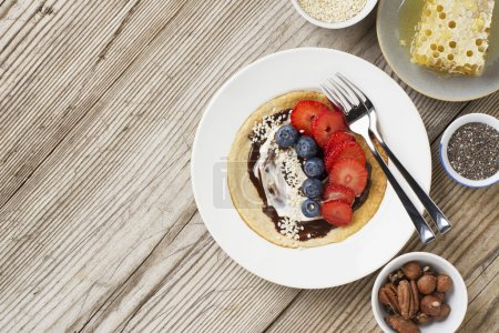 Oatmeal pancakes in a frying pan on wooden table