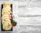 Festive Christmas card. Homemade cookies with chocolate drops for Santa Claus in the baking dish is decorated  fir branches, red balls, cones, candy striped staffs. selective focus