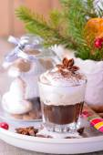 Winter whipped cream hot coffee in a glass cup with anise and cinnamon