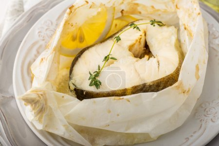 Foto de Cod fillets  baked in parchment paper with slices of lemon and a sprig of thyme on light dishes. Selective focus. Concept of healthy food. - Imagen libre de derechos
