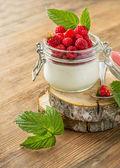 Glass jar with homemade yogurt and fresh garden raspberries