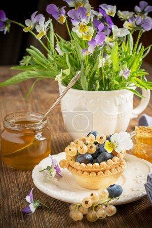Photo pour Tartelette pâtissière croquante fraîche légère de bleuets frais et de groseilles blanches sur des plats à la carte avec peigne de miel en arrière-plan Bunch d'alto sur un fond en bois. Focus sélectif - image libre de droit