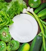 White ceramic plate surrounded by a variety of green vegetables
