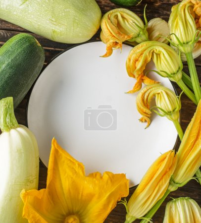 White ceramic plate surrounded by fresh flowers and colorful fruits of zucchini