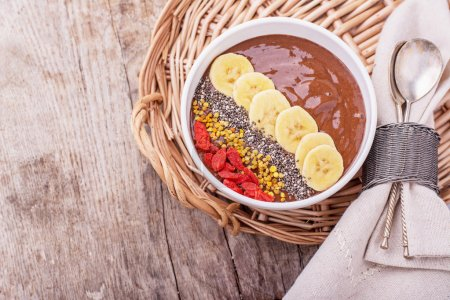 Chocolate banana pudding garnished with bee pollen, goji berries, chia seeds