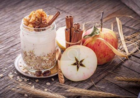 Photo pour Nuit gruau avec du yaourt, pot de tranches de pommes fraîches dans le lot de cannelle dans un verre sur un fond en bois avec des pommes, de bâtons de cannelle et de miel. Le concept de saine des aliments naturels. mise au point sélective - image libre de droit