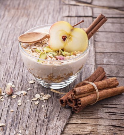 Photo pour Gruau au jour le jour avec yogourt, cannelle moulue et tranche de pomme dans un bol en verre sur un fond en bois avec du miel, pistaches, cannelle et apple. Le concept d'aliments sains. mise au point sélective - image libre de droit