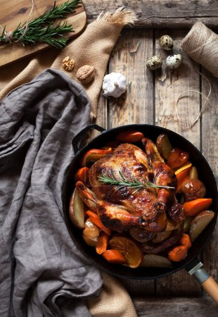 Photo for Roasted chicken with brown crispy skin stuffed with various vegetables and spices, garlic in cast iron skillet on vintage wooden table background. Rustic style, top view. - Royalty Free Image