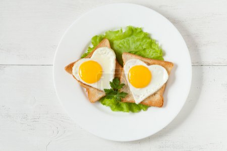 Photo for Concept of super food breakfast or lunch - slices of wholewheat toast with two fried eggs, salad and parsley on white dish - Royalty Free Image