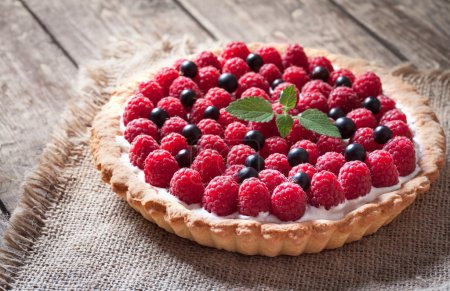 Delicious traditional homemade sweet raspberry tart cake dessert. Creamy pie with raspberries, whipped cream and mint on vintage rustic background.