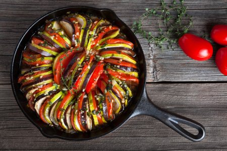 Vegetable ratatouille baked in cast iron frying pan traditional homemade healthy diet french vegetarian food on vintage wooden table background. Top view.