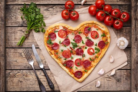Photo pour Heart shaped pizza for Valentines day with pepperoni, mozzarella, tomatoes, parsley and garlic on vintage wooden table background. Food symbol of romantic love.  Rustic style. Top View - image libre de droit
