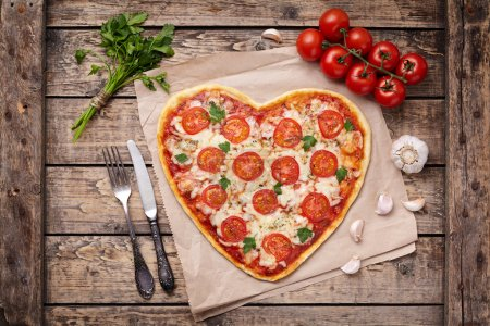 Heart shaped pizza margherita love concept for Valentines Day with mozzarella, tomatoes, parsley and garlic on vintage wooden table background.