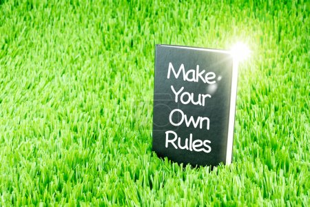 """Shining Black book on grass with """" Make your own rules """" word, B"""