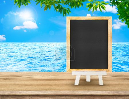 Blackboard menu with easel on wood table at sea with tree and su
