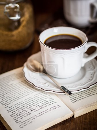 Cup of coffee with open book