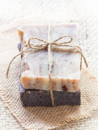 Photo pour Photo verticale de deux barres de chocolat et de savon de baobab fabriqués à la main sur un fond de toile de jute. Vue aérienne, plan rapproché. - image libre de droit