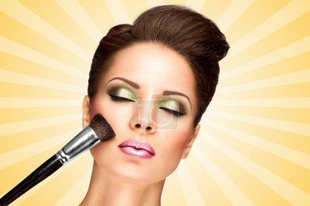 Photo for Glamour girl with retro fashion hairstyle applying dry cosmetic tonal foundation on the face using makeup brush on colorful abstract cartoon style background. - Royalty Free Image