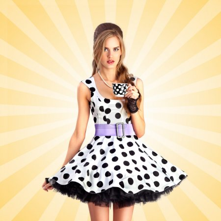 Teatime in dots. Creative vintage photo of a beautiful pin-up girl in a polka dot dress, holding a cup of tea on colorful abstract cartoon style background.