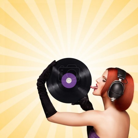 Taste and listen. Colorful photo of a seductive girl, wearing huge vintage music headphones and licking a purple LP microgroove vinyl record on colorful abstract cartoon style background.
