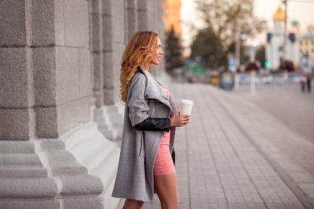 City espresso. A pretty woman with a coffee to go against urban scene.