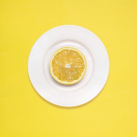 Lemon for breakfast. Lemon slice on white plate on yellow background.