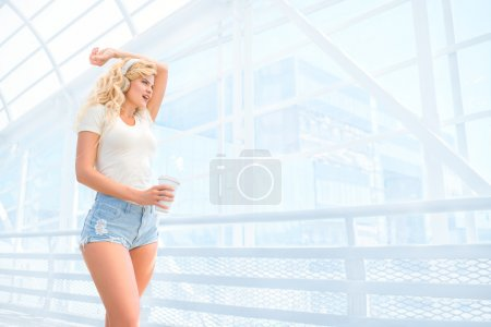 Morning walks. Beautiful young woman with music headphones, standing on the bridge with a take away coffee cup and posing against urban background.