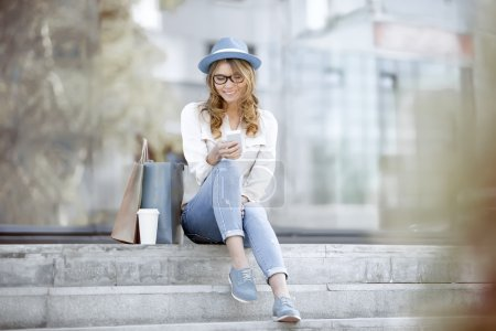 Photo for Happy young woman with a disposable coffee cup and shopping bags sitting on the stairs and using her smartphone for communication via wi-fi internet in a summer park. - Royalty Free Image