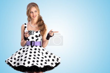 Photo for A creative vintage photo of a beautiful pin-up girl in a polka dot dress holding a cup of tea. - Royalty Free Image