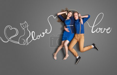 Photo pour Heureuse Saint-Valentin amour concept histoire d'un couple romantique, écoutant de la musique d'amour sur fond de dessins de craie de paroles et de partage des écouteurs. - image libre de droit