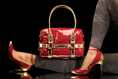 Photo for A close-up of a chic red handbag along with sexy female legs wearing elegant red shoes. - Royalty Free Image