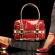 A close-up of a chic red handbag along with sexy f...